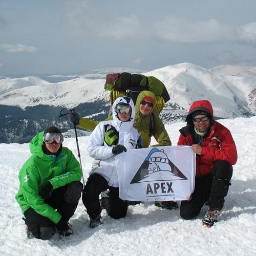 Наши гиды на вершине горы с флагом компании